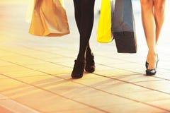 Πόδια γυναικών με τις τσάντες αγορών που πηγαίνουν στη μεγάλη πώληση Στοκ Εικόνες