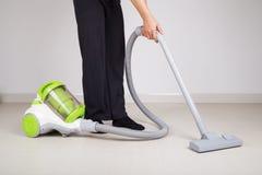 Πόδια γυναικών με το καθαρίζοντας πάτωμα ηλεκτρικών σκουπών στοκ φωτογραφία