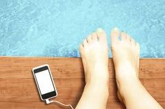 Πόδια γυναικών με το κενό smartphone οθόνης στην πισίνα - liste Στοκ εικόνες με δικαίωμα ελεύθερης χρήσης
