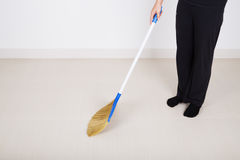 Πόδια γυναικών με το σκουπίζοντας πάτωμα σκουπών Στοκ Εικόνες