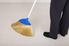 Πόδια γυναικών με το σκουπίζοντας πάτωμα σκουπών Στοκ εικόνες με δικαίωμα ελεύθερης χρήσης