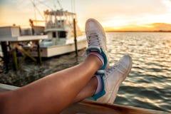 Πόδια γυναικών πέρα από τον κόλπο θάλασσας και γιοτ στο χρόνο ηλιοβασιλέματος στοκ φωτογραφία με δικαίωμα ελεύθερης χρήσης