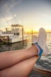 Πόδια γυναικών που χαλαρώνουν στο γιοτ στον κόλπο θάλασσας στοκ φωτογραφίες