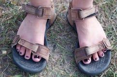 Πόδια γυναικών στα αθλητικά σανδάλια στον πράσινο τομέα Στοκ Εικόνες
