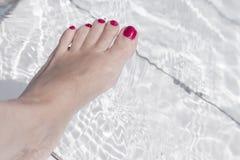 Πόδια γυναικών στο νερό λιμνών Στοκ εικόνες με δικαίωμα ελεύθερης χρήσης