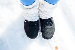 Πόδια γυναικών ` s στα μοντέρνα τρέχοντας παπούτσια στο χιόνι Στοκ εικόνες με δικαίωμα ελεύθερης χρήσης