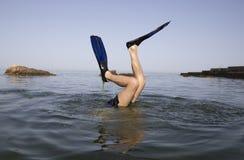Πόδια ενός βουτώντας ατόμου στα μαύρα πτερύγια για την κολύμβηση επάνω από το surfac Στοκ Φωτογραφία