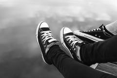 Πόδια ζευγών στα πάνινα παπούτσια που χαλαρώνουν από το νερό Στοκ εικόνες με δικαίωμα ελεύθερης χρήσης