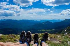 Πόδια ζεύγους στην αιχμή του λόφου που κοιτάζει στα βουνά και τον όμορφο ουρανό στη θερινή ημέρα, πρώτη άποψη προσώπων Στοκ Εικόνα