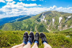 Πόδια ζεύγους στην αιχμή του λόφου που κοιτάζει στα βουνά και τον όμορφο ουρανό στη θερινή ημέρα, πρώτη άποψη προσώπων Στοκ φωτογραφίες με δικαίωμα ελεύθερης χρήσης