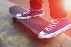 Πόδια και ο πίνακας skateboarder στην έναρξη, ηλιόλουστο βράδυ Στοκ εικόνες με δικαίωμα ελεύθερης χρήσης