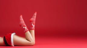 Πόδια κας Άγιος Βασίλης στις γυναικείες κάλτσες Χριστουγέννων Στοκ Φωτογραφία