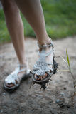 Πόδια κοριτσιών στα βρώμικα σανδάλια Στοκ Εικόνα