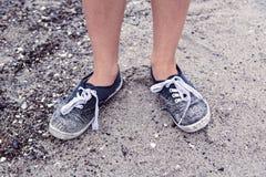 Πόδια με τα παλαιά βρώμικα μπλε παπούτσια στην παραλία Στοκ εικόνα με δικαίωμα ελεύθερης χρήσης