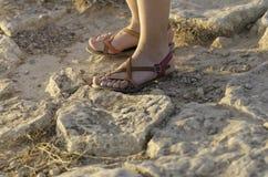 Πόδια με τα σανδάλια στο βράχο στοκ εικόνες