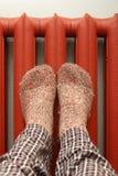 Πόδια με τις κάλτσες μαλλιού που θερμαίνουν στο θερμαντικό σώμα Στοκ εικόνες με δικαίωμα ελεύθερης χρήσης