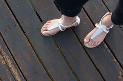 Πόδια μικρών κοριτσιών στα άσπρα σανδάλια Στοκ Φωτογραφία
