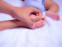 Πόδια μωρών στο χέρι γονέων Στοκ Φωτογραφίες