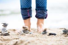 Πόδια παιδιών και πυραμίδες πετρών στην άμμο Θάλασσα στην ανασκόπηση Στοκ Εικόνες