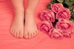 Πόδια παιδιών με τα ρόδινα λουλούδια Στοκ εικόνα με δικαίωμα ελεύθερης χρήσης