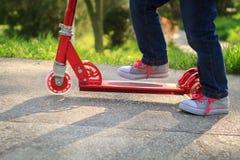 Πόδια παιδιών σε ένα μηχανικό δίκυκλο λακτίσματος Στοκ φωτογραφία με δικαίωμα ελεύθερης χρήσης