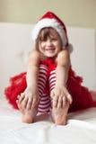 Πόδια παιδιών στα ριγωτά κατώτατα σημεία πυτζαμών του νέου έτους στο κρεβάτι, Στοκ Φωτογραφία