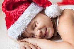 Πόδια παιδιών στα ριγωτά κατώτατα σημεία πυτζαμών του νέου έτους στο κρεβάτι, Στοκ Φωτογραφίες