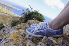 Πόδια παπουτσιών γυναικών στον απότομο βράχο βουνών Στοκ Φωτογραφίες