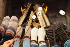 Πόδια που θερμαίνουν σε μια εστία με marshmallows στα ραβδιά στοκ εικόνες