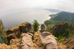 Πόδια που κρεμούν πέρα από τη τοπ άποψη βράχου απότομων βράχων _ Στοκ φωτογραφίες με δικαίωμα ελεύθερης χρήσης