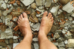 Πόδια που στέκονται στις συγκεκριμένες πέτρες Στοκ Εικόνα