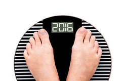 2016 πόδια σε μια κλίμακα βάρους που απομονώνεται στο λευκό Στοκ εικόνα με δικαίωμα ελεύθερης χρήσης