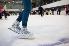 Πόδια σκέιτερ στην κίνηση στην αίθουσα παγοδρομίας πάγου με πολλά Στοκ Φωτογραφία