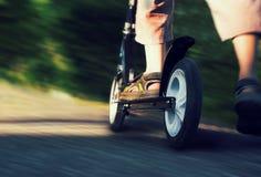 Πόδια στα σανδάλια που στέκονται στο μηχανικό δίκυκλο Στοκ εικόνα με δικαίωμα ελεύθερης χρήσης