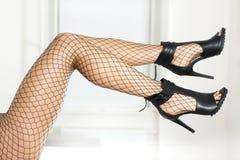 Πόδια στις γυναικείες κάλτσες διχτυών ψαρέματος και τα μοντέρνα υψηλά τακούνια Στοκ Φωτογραφίες