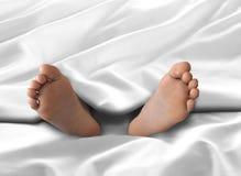 Πόδια στο πλαίσιο του άσπρου φύλλου καλυμμάτων και κρεβατιών Στοκ Φωτογραφία
