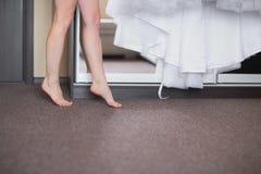 Πόδια της γυναίκας που στέκονται tiptoe στο σπίτι γάμος κατάταξης τεμαχίων φορεμάτων Στοκ Φωτογραφίες