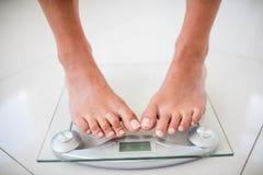 Πόδια της γυναίκας στη στάθμιση της κλίμακας Στοκ εικόνες με δικαίωμα ελεύθερης χρήσης