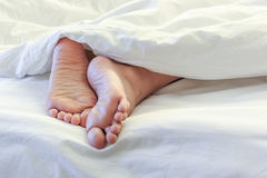 Πόδια της γυναίκας ύπνου στο άσπρο δωμάτιο κρεβατιών Στοκ Φωτογραφίες