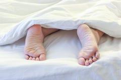 Πόδια της γυναίκας ύπνου στο άσπρο δωμάτιο κρεβατιών Στοκ εικόνα με δικαίωμα ελεύθερης χρήσης