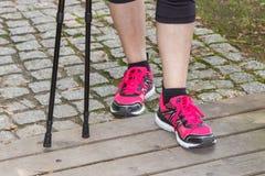 Πόδια της ηλικιωμένης ανώτερης γυναίκας και των σκανδιναβικών ραβδιών περπατήματος, φίλαθλοι τρόποι ζωής στοκ εικόνα