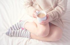 Πόδια της θερμής μάλλινης θέρμανσης καλτσών και φλιτζανιών του καφέ κοριτσιών, χειμερινό πρωί στο κρεβάτι Στοκ Φωτογραφίες