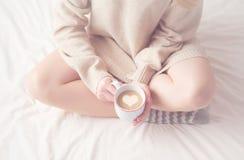 Πόδια της θερμής μάλλινης θέρμανσης καλτσών και φλιτζανιών του καφέ κοριτσιών, χειμερινό πρωί στο κρεβάτι Στοκ Εικόνα