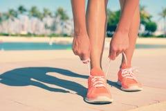 Πόδια της κατάλληλης δαντέλλας αθλητικών παπουτσιών γυναικών δένοντας Στοκ Εικόνες