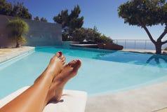 Πόδια της νέας κυρίας που κάνει ηλιοθεραπεία από την πισίνα Στοκ Εικόνες