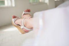 Πόδια της νύφης στα γαμήλια παπούτσια Στοκ Φωτογραφίες
