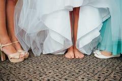 Πόδια της όμορφης νύφης στα παπούτσια και το άσπρο φόρεμα Στοκ Φωτογραφία