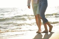 Πόδια του ζεύγους στην παραλία άμμου στοκ εικόνες
