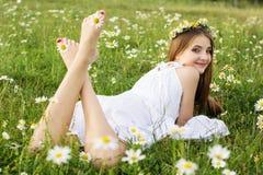 Πόδια του κοριτσιού παιδιών με τα chamomiles Στοκ φωτογραφία με δικαίωμα ελεύθερης χρήσης