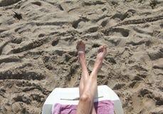 Τα διασχισμένα γυμνά πόδια ενάντια στην κίτρινη άμμο θάλασσας Στοκ Εικόνα